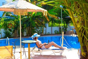 34045243 - relaxing by the pool ; young woman relaxes by the pool with a laptop